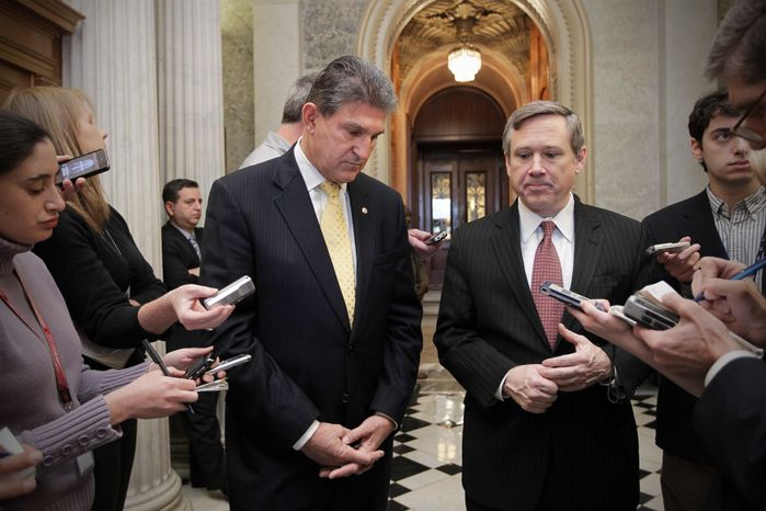 Sen. Joe Manchin III (left), West Virginia Democrat, and Sen. Mark Kirk, Illinois Republican, comment as the Senate approves legislation that extends Social Security payroll tax cuts for two months, at the Capitol in Washington on Saturday, Dec. 17, 2011. (AP Photo/J. Scott Applewhite)