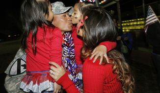 U.S. Army Staff Sgt. Elama Palemene greets his wife, Annaden (right), and children Ko' Elani (left) and Pe' Ela during an early morning welcome-home ceremony at Fort Hood, Texas, for about 300 soldiers returning home from deployment in Iraq on Sunday, Dec. 18, 2011. (AP Photo/Erich Schlegel)