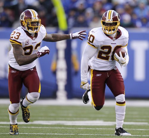 Washington Redskins' Oshiomogho Atogwe, right, runs the ball back after intercepting a pass as teammate DeAngelo Hall runs next to him during the second quarter against the New York Giants, Sunday, Dec. 18, 2011, in East Rutherford, N.J. (AP Photo/Kathy Willens)