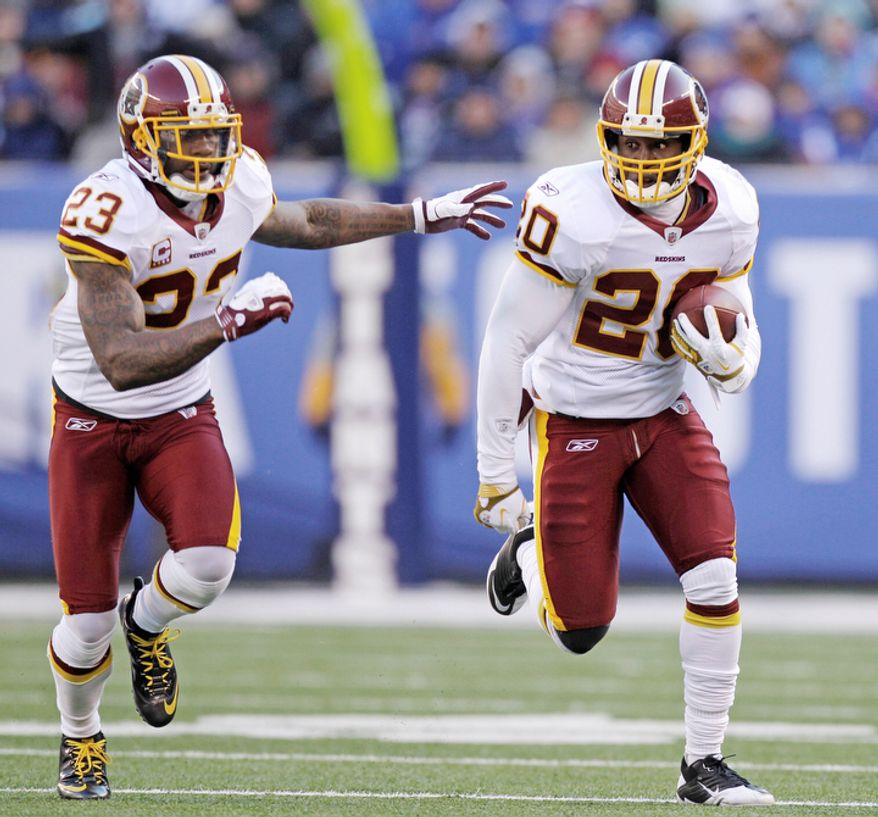 Washington Redskins' Oshiomogho Atogwe, right, runs the ball back after intercepting a pass as teammate DeAngelo Hall runs next to him during the second quarter. (AP Photo/Kathy Willens)