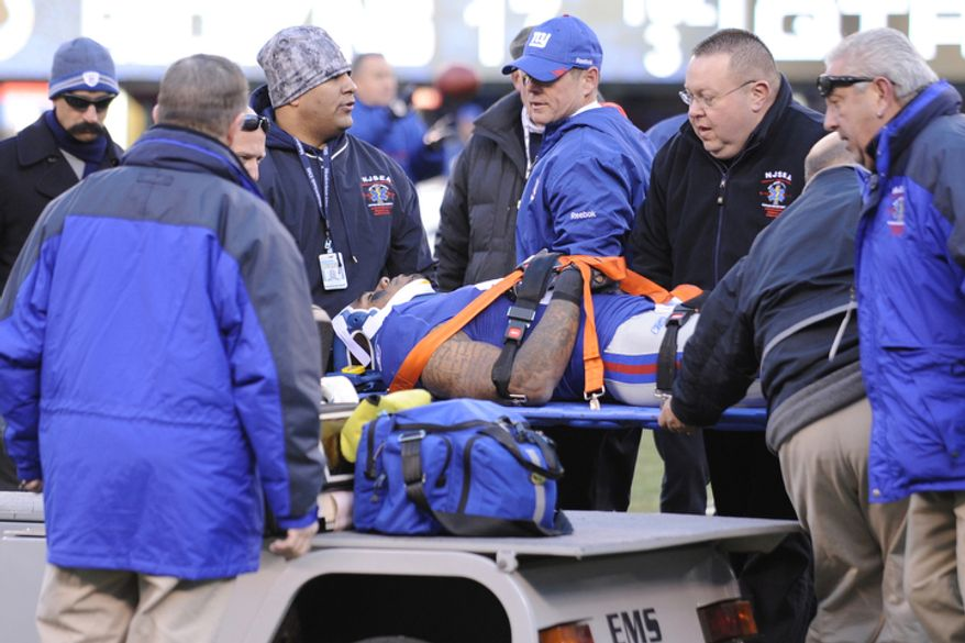 New York Giants' Devin Thomas, center, is brought off the field after being injured during the second quarter. (AP Photo/Bill Kostroun)