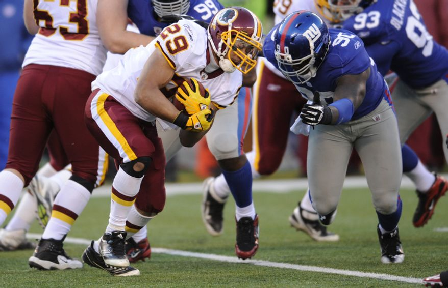 Washington Redskins' Roy Helu, left, is tackled by New York Giants' Jason Pierre-Paul during the second quarter. (AP Photo/Bill Kostroun)