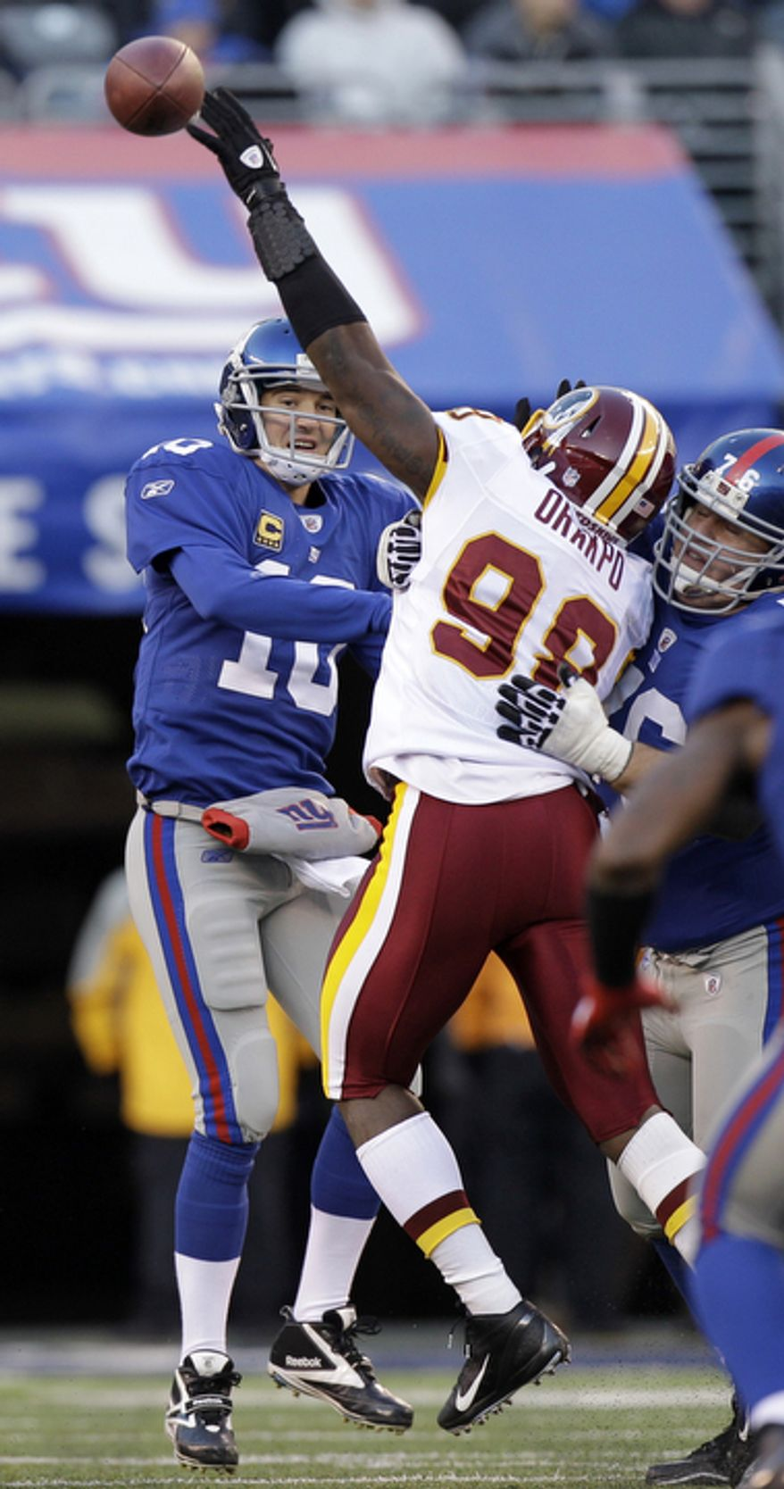 Washington Redskins' Brian Orakpo, right, tries to get a hand on a pass from New York Giants' Eli Manning during the third quarter. (AP Photo/Kathy Willens)
