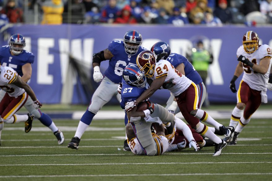 New York Giants running back Brandon Jacobs (27) is tackled by Washington Redskins strong safety DeJon Gomes (24) and inside linebacker London Fletcher, bottom, during the third quarter. (AP Photo/Kathy Willens)