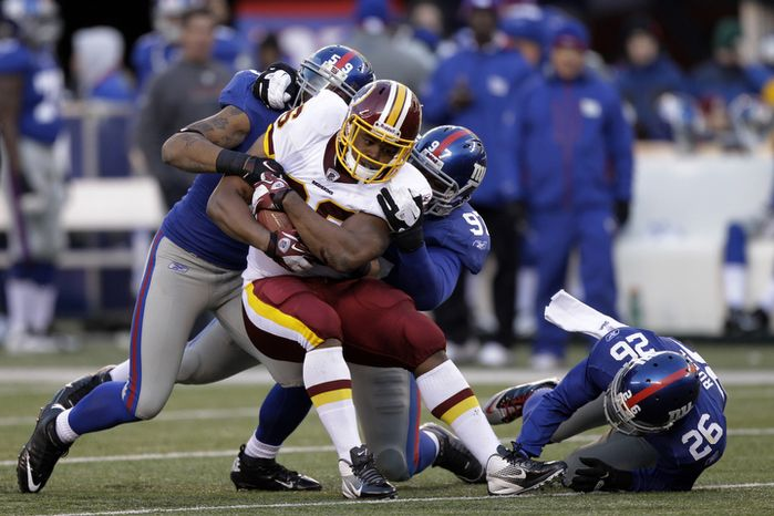 Washington Redskins fullback Darrel Young (36) is tackled by New York Giants outside linebacker Michael Boley (59) and defensive tackle Linval Joseph during the third quarter. (AP Photo/Kathy Willens)