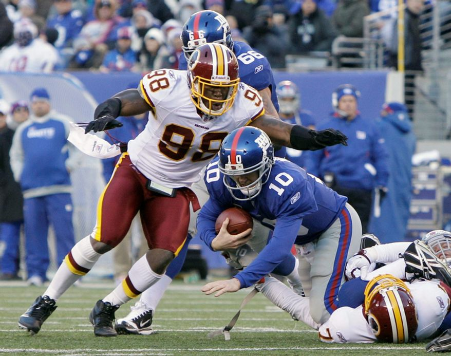 Washington Redskins' Brian Orakpo, left, jumps on New York Giants' Eli Manning, center, after Manning was sacked by Redskins' Stephen Bowen, bottom right, during the third quarter. (AP Photo/Kathy Willens)