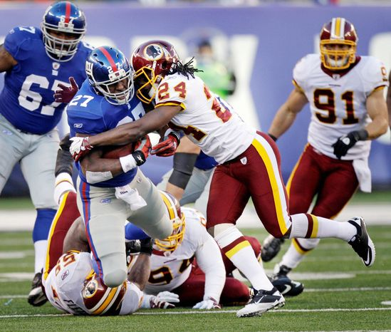 New York Giants' Brandon Jacobs, left, is tackled by Washington Redskins' DeJon Gomes during the third quarter. (AP Photo/Kathy Willens)