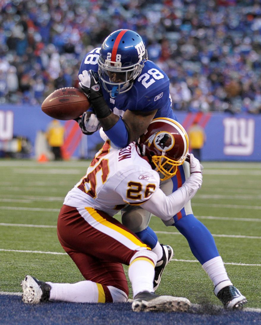 New York Giants' D.J. Ware, top, bobbles the ball while being tackled by Washington Redskins' Josh Wilson on the goal line during the fourth quarter. (AP Photo/Julio Cortez)