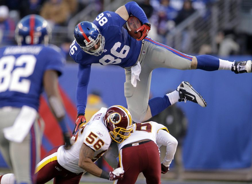 New York Giants' Bear Pascoe, top, leaps over Washington Redskins defenders during the fourth quarter. (AP Photo/Julio Cortez)