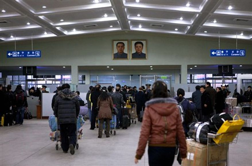 Under framed portraits of the late North Korean leaders Kim Il-sung (left) and his son, Kim Jong-il, airline passengers arrive at the Pyongyang, North Korea, airport on Monday, Dec. 19, 2011. North Korean state media reported Monday that Kim Jong-il died on Saturday of a heart attack. (AP Photo/David Guttenfelder)