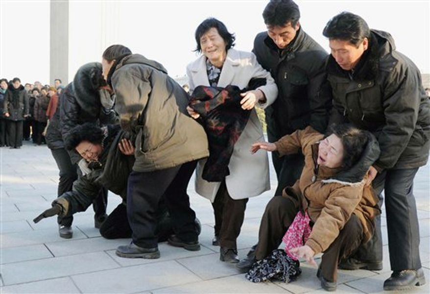Women collapse in tears as North Koreans gather on Monday, Dec. 19, 2011, in Pyongyang, North Korea, after learning of the death of their leader, Kim Jong-il. (AP Photo/Kyodo News)
