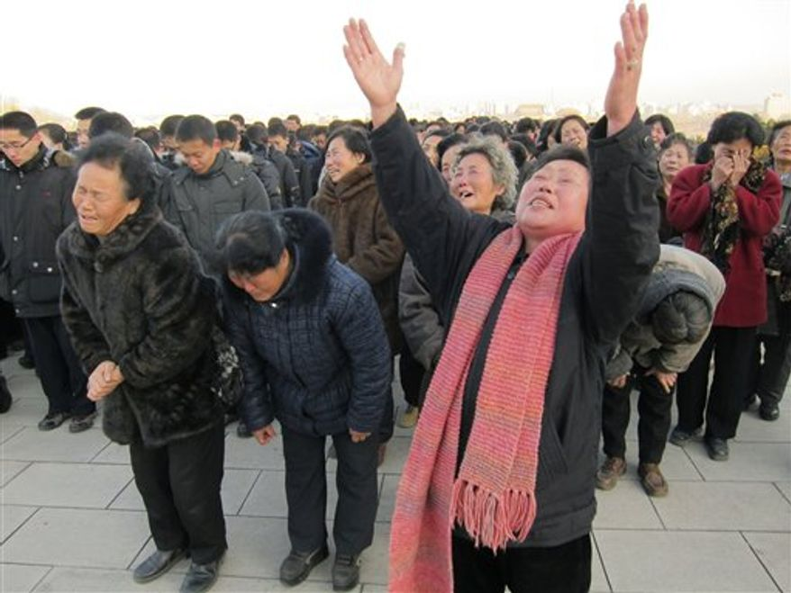 North Koreans cry and scream in a display of mourning for their leader, Kim Jong-il, at the foot of a giant statue of his father, Kim Il-sung, in Pyongyang, North Korea, after Kim Jong-il's death was announced on Monday, Dec. 19, 2011. (AP Photo/APTN)