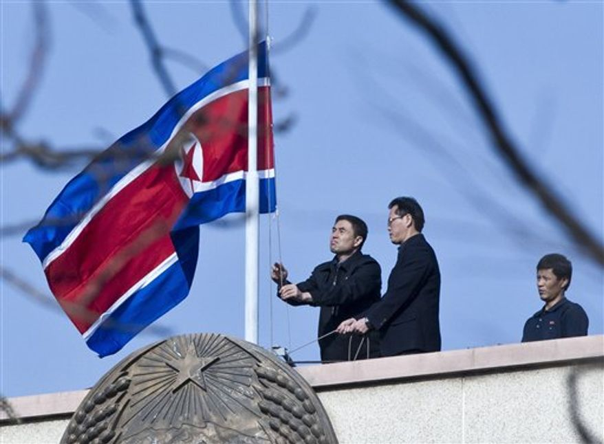 North Korean diplomatic staff lower their national flag to half-mast on the roof of their embassy in Beijing on Monday, Dec. 19, 2011, to mourn the death of the country's leader, Kim Jong-il. (AP Photo/Andy Wong)