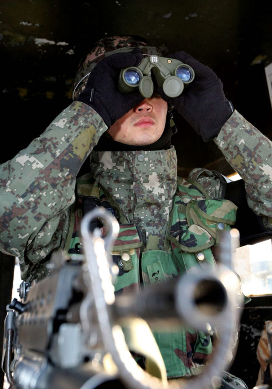 A South Korean soldier uses binoculars to watch North Korea from a guard post in the demilitarized zone between the two Koreas in Cheolwon, South Korea, on Monday, Dec. 19, 2011, after news of the death of North Korean leader Kim Jong-il. (AP Photo/Yonhap, Lee Hae-ryoung)