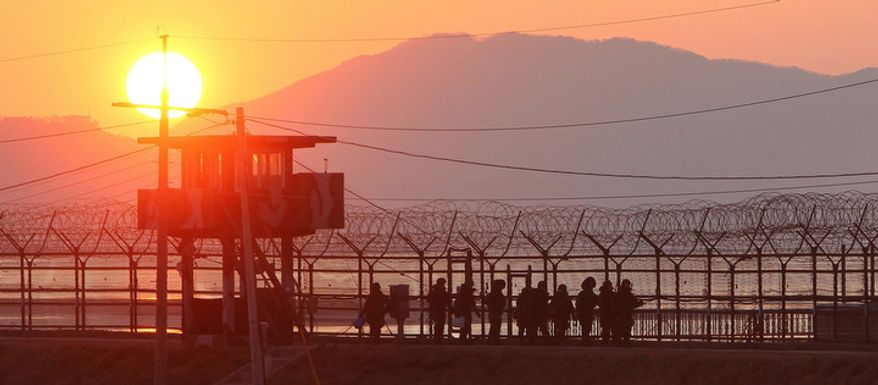 South Korean soldiers patrol along the barbed-wire fence near the demilitarized zone in Paju, South Korea, before sunset on Monday, Dec. 19, 2011. Kim Jong-il, North Korea's mercurial and enigmatic leader, has died. He was 69. (AP Photo/Yonhap, Lee Myung-shik)