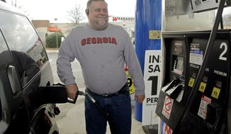 In this Dec. 15, 2011 photo, Michael Reed fills his gas tank at a station in Charlotte, N.C. The retail price of gasoline averaged more than $3.50 per gallon for the year, a record. Drivers cut back where they could, driving less and switching to more fuel efficient cars. (AP Photo/Chuck Burton)