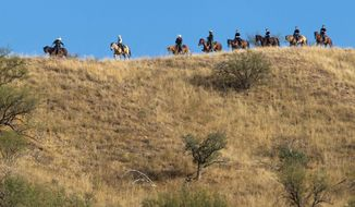 Homeland Security Secretary Janet A. Napolitano (riding fifth horse from left) tours the U.S.-Mexico border with Border Patrol agents in the Coronado National Forest near Nogales, Ariz., in October. Starting in January, the force of 1,200 National Guard troops at the border will be reduced to fewer than 300 at a cost of about $60 million. (Associated Press)