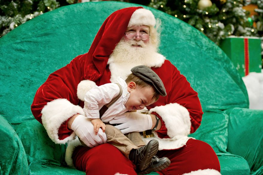 Not everyone is happy to visit Santa Claus the first time around. Thiago Heath, 18 months old, of Falls Church, was making his first visit to Santa at Tysons Corner Center and was having second thoughts about it. (Andrew Harnik/The Washington Times)