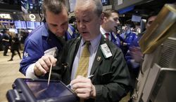 Traders James Lodewick (left) and James Riley (center) work on the floor of the New York Stock Exchange on Tuesday, Dec. 20, 2011. (AP Photo/Richard Drew)