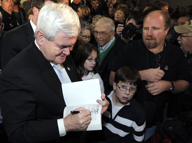 Former House Speaker Newt Gingrich, campaigning for the GOP presidential nomination, autographs a book before a stop at Global Security Services in Davenport, Iowa, on Monday, Dec. 19, 2011. (AP Photo/Chris Carlson)