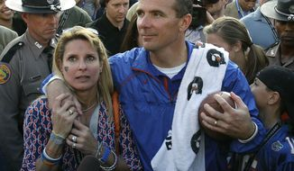 ** FILE ** In this Jan. 1, 2011, file photo, Florida head coach Urban Meyer puts his arm around his wife Shelley after Florida defeated Penn State 37-24 in the Outback Bowl NCAA college football game, in Tampa, Fla. (AP Photo/Chris O'Meara, File)