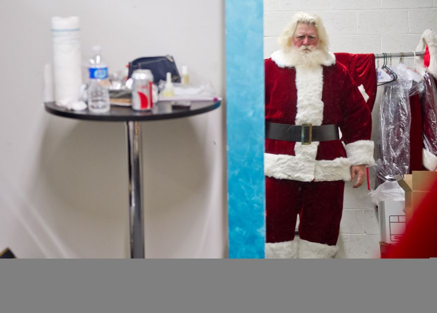 Michael Graham, who plays Santa, checks himself the the mirror in his dressing room as he gets ready for his morning shift. (Andrew Harnik / The Washington Times)