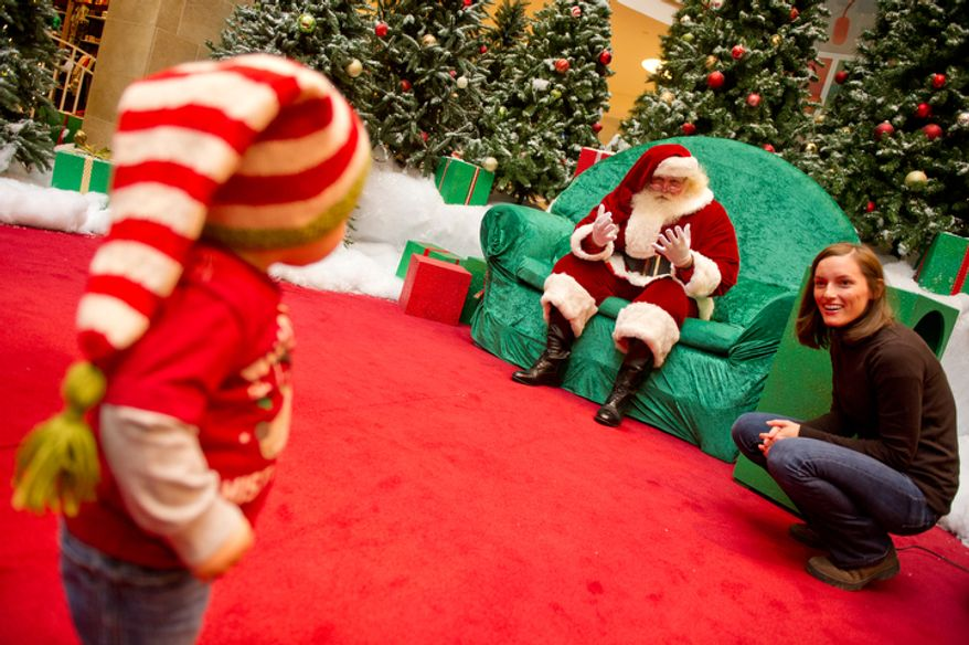 Michael Graham, who plays Santa at Tyson's Corner Center tries to coerce 14 month year old Brody Spaulding of Falls Church, VA into coming to sit on his lap with the help of Brody's Mother, Liz. (Andrew Harnik / The Washington Times)