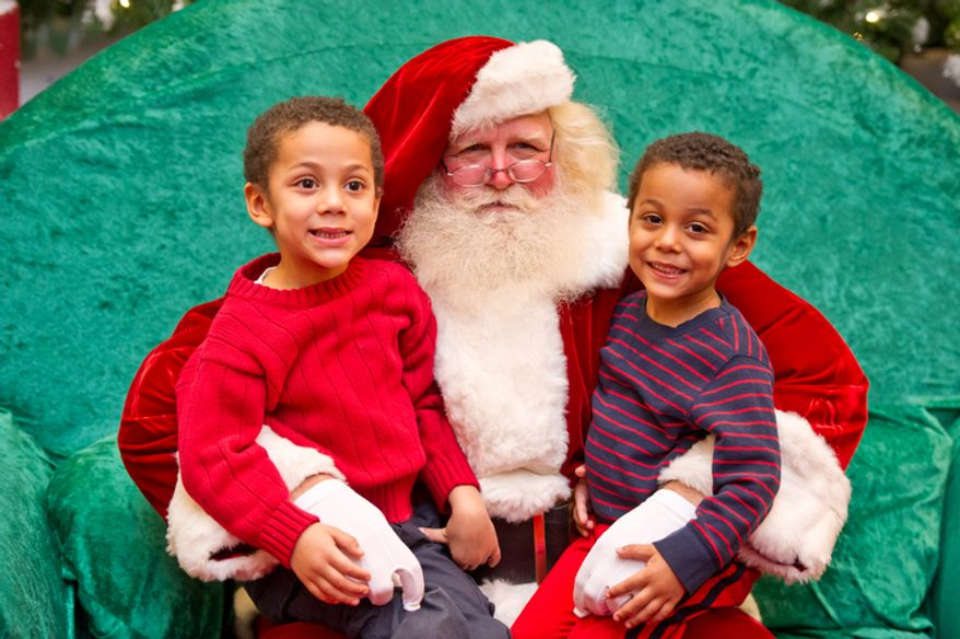 5 year old Daniel Cline-Thomas, left, of Falls Church, VA and his 3 year old brother Michael, right, smile for the camera as they sit on the lap of Santa, played by Michael Graham. (Andrew Harnik / The Washington Times)
