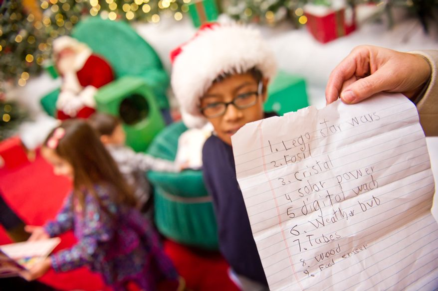 9-year-old Benjamin Hawley, center, of Arlington, VA, gives his Christmas list back to his mother after visiting with Santa. (Andrew Harnik / The Washington Times)