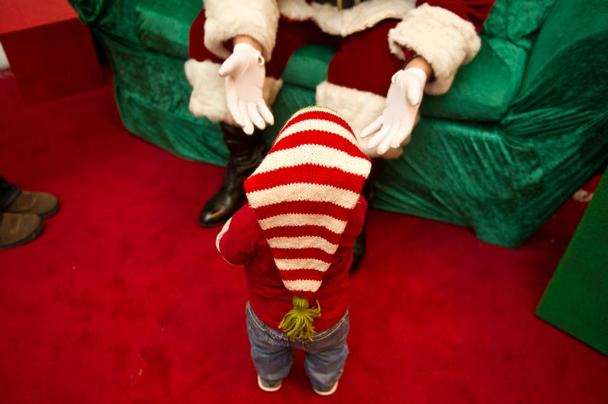 Michael Graham, who plays Santa at Tyson's Corner Center tries to coerce 14 month year old Brody Spaulding of Falls Church, VA into coming to sit on his lap, Tyson's Corner, VA, Wednesday, December 14, 2011. (Andrew Harnik / The Washington Times)