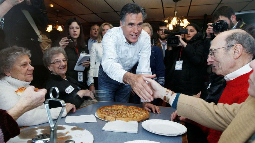 PIZZA PARLOR POLITICIAN: Former Massachusetts Gov. Mitt Romney, a Republican presidential contender, shakes hands with patrons while campaigning at Village Pizza in Newport, N.H. (Associated Press)