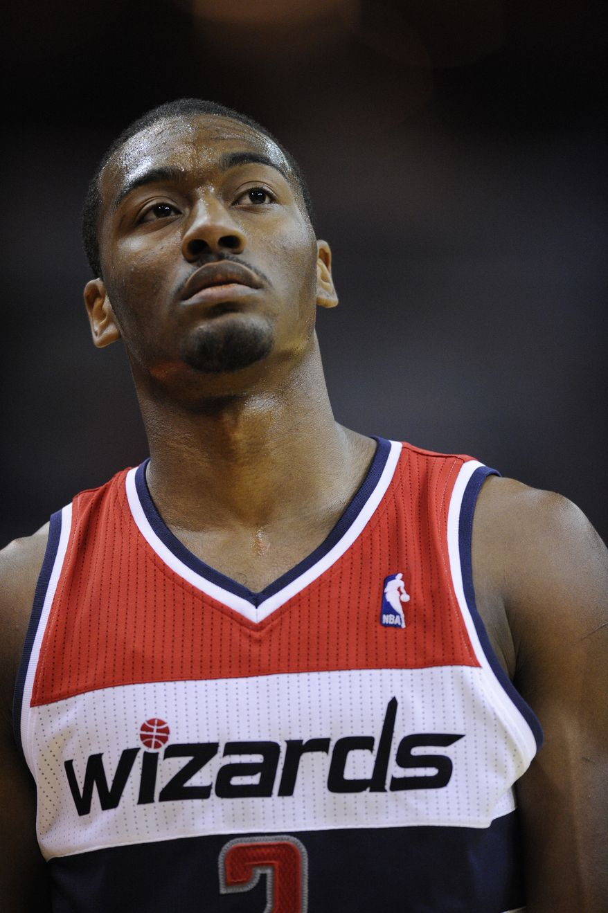Washington Wizards point guard John Wall looks on during the second half of his team's first preseason game against the Philadelphia 76ers, Friday, Dec. 16, 2011, in Washington. The 76ers won 103-78. The Wizards lost the second game, but showed improvement, losing 101-94 in Philadelphia. (AP Photo/Nick Wass)