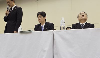 """Tokyo Electric Power Co. President Toshio Nishizawa, right, looks up as Japan's Nuclear Crisis Minister Goshi Hosono, left, speaks during a press conference at the headquarters of TEPCO, the operator of the tsunami-damaged Fukushima Dai-ichi nuclear power plant, in Tokyo Friday, Dec. 16, 2011, shortly after Japan's prime minister announced that the nuclear plant has achieved a stable state of """"cold shutdown,"""" a crucial step toward the eventual lifting of evacuation orders and closing of the plant. (AP Photo/Hiro Komae)"""
