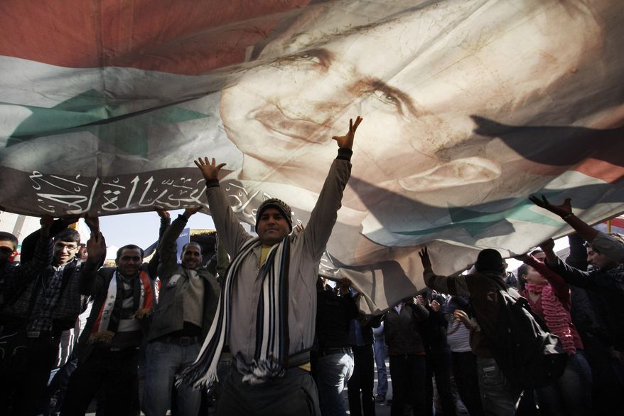 A demonstrator gestures under a large poster of Syrian President Bashar Assad during a rally in Damascus, Syria, on Monday, Dec. 19, 2011. (AP Photo/Muzaffar Salman)