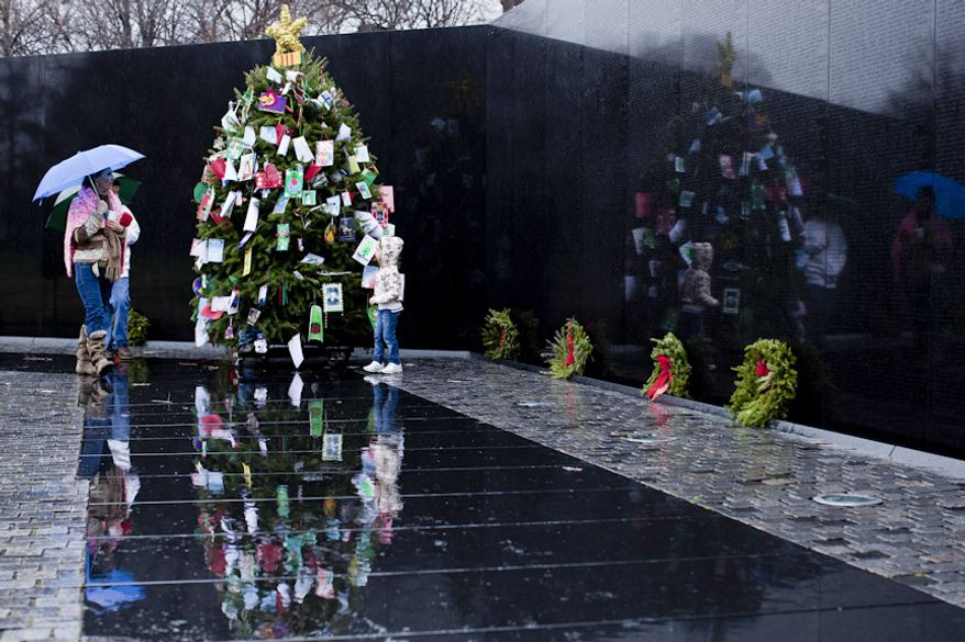 """Raene Hicks, of Vale, Ore., from left, with her son Lain, 12, and daughter Sally, 5, look at the Christmas tree in the Vietnam Memorial in Washington, D.C. on Dec. 21, 2011. Raene said both her father and grandfather fought in the Vietnam War aboard the same Navy ship. """"Both made it home, my family is blessed,"""" she said, adding that """"I come out here to see if I recognize any other names."""" (T.J. Kirkpatrick/ The Washington Times)"""