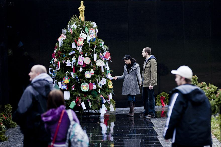 Selena Hajiani, at center, with William Hynes, both of Albany, N.Y., holds an ornament with a photograph of a soldier who went missing in the Vietnam War, on the Christmas tree at the Vietnam Memorial in Washington, D.C. on Dec. 21, 2011. (T.J. Kirkpatrick/ The Washington Times)