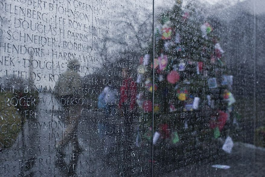 Visitors are seen reflected in the rain streaked Vietnam Memorial wall by the Christmas tree in the Vietnam Memorial in Washington, D.C. on Dec. 21, 2011. (T.J. Kirkpatrick/ The Washington Times)