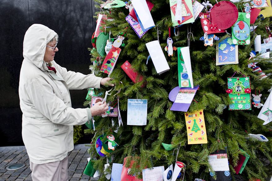 """Shirley Salchert of Vancouver, British Columbia, replaces an ornament that fell off of the Christmas tree at the Vietnam Veterans Memorial in Washington on Wednesday, Dec. 21, 2011. """"It's a moving place to be,"""" said Ms. Salchert, on a visit with her son, who works for the North American Aerospace Defense Command. (T.J. Kirkpatrick/The Washington Times)"""