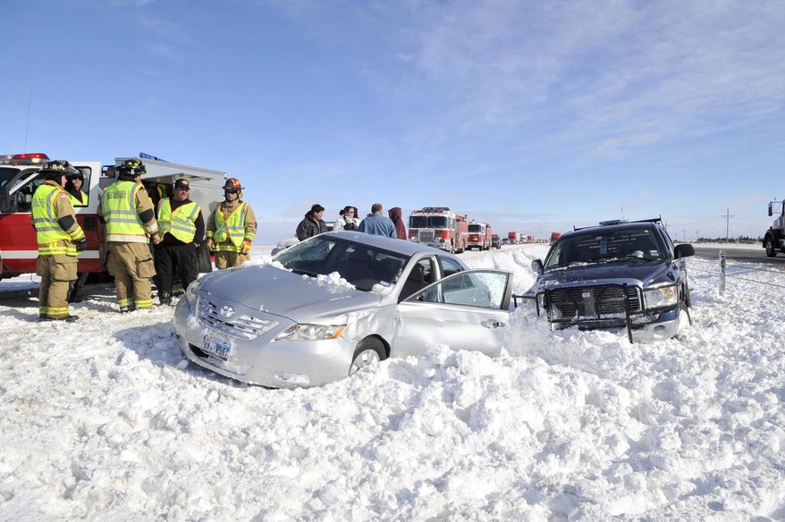 Emergency responders assists victims of a multiple-vehicle accident on westbound Interstate 40 about 15 miles west of Amarillo, Texas, on Tuesday, Dec. 20, 2011. (AP Photo/The Amarillo Globe News, Michael Schumacher)
