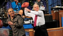 "In this photo released by CBS, host David Letterman, right, and comic Jay Thomas get ready to throw footballs at the Late Show Christmas tree during the annual Late Show Holiday Quarterback Challenge on the set of ""Late Show with David Letterman,"" airing Thursday, Dec. 23, 2011 on the CBS Television Network. Thomas and Letterman each take turns tossing footballs at the Late Show Christmas tree to try and knock off the giant meatball perched at its top. (AP Photo/CBS, John Paul Filo)"