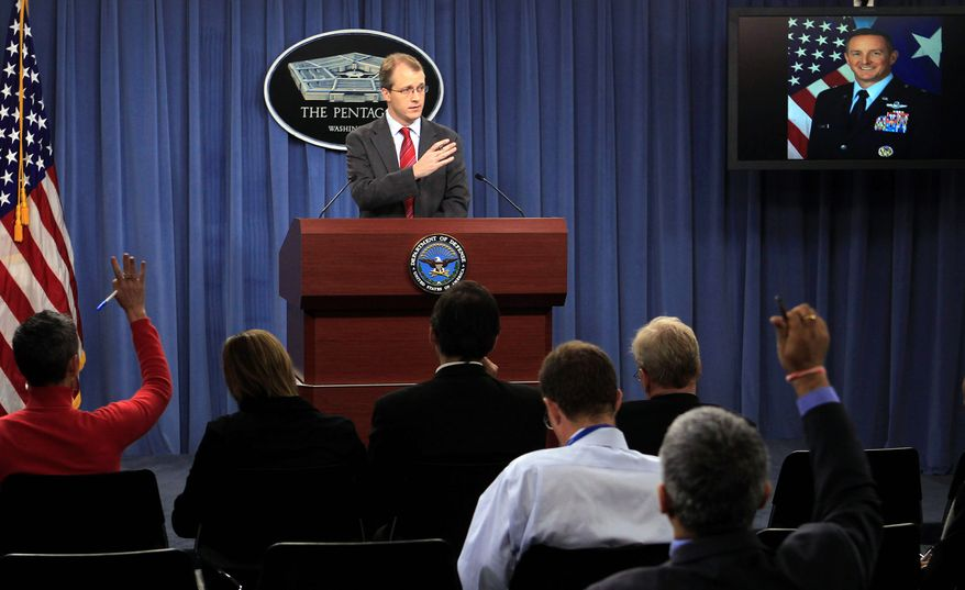 ** FILE ** Pentagon press secretary George Little (center) takes part in an audio news conference with Brig. Gen. Stephen A. Clark of the Air Force Special Operations Command (pictured on a television top right) at the Pentagon on Thursday, Dec. 22, 2011. (Associated Press)