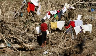 ASSOCIATED PRESS A resident of Cagayan de Oro in the southern Philippines dries his clothes on toppled trees along a riverbank on Thursday. Flash flooding Dec. 16 killed more than 1,000 people.
