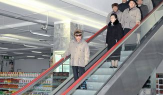 "A final photograph of Kim Jong-il, released Saturday, shows North Korea's ""Dear Leader"" in a Pyongyang grocery store with a retinue that includes his son-successor, Kim Jong-un (right on the first step with two riders),  Kim Jong-il's sister Kim Kyong-hui and her husband, Jang Song-thaek (two steps behind Kim Jong-un, in light jacket). (Associated Press)"