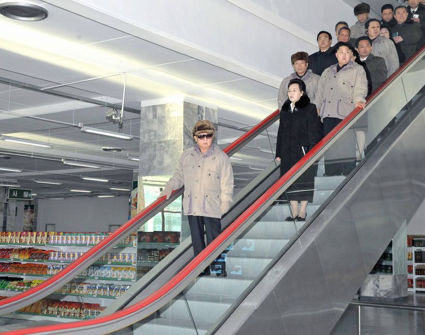 """A final photograph of Kim Jong-il, released Saturday, shows North Korea's """"Dear Leader"""" in a Pyongyang grocery store with a retinue that includes his son-successor, Kim Jong-un (right on the first step with two riders),  Kim Jong-il's sister Kim Kyong-hui and her husband, Jang Song-thaek (two steps behind Kim Jong-un, in light jacket). (Associated Press)"""