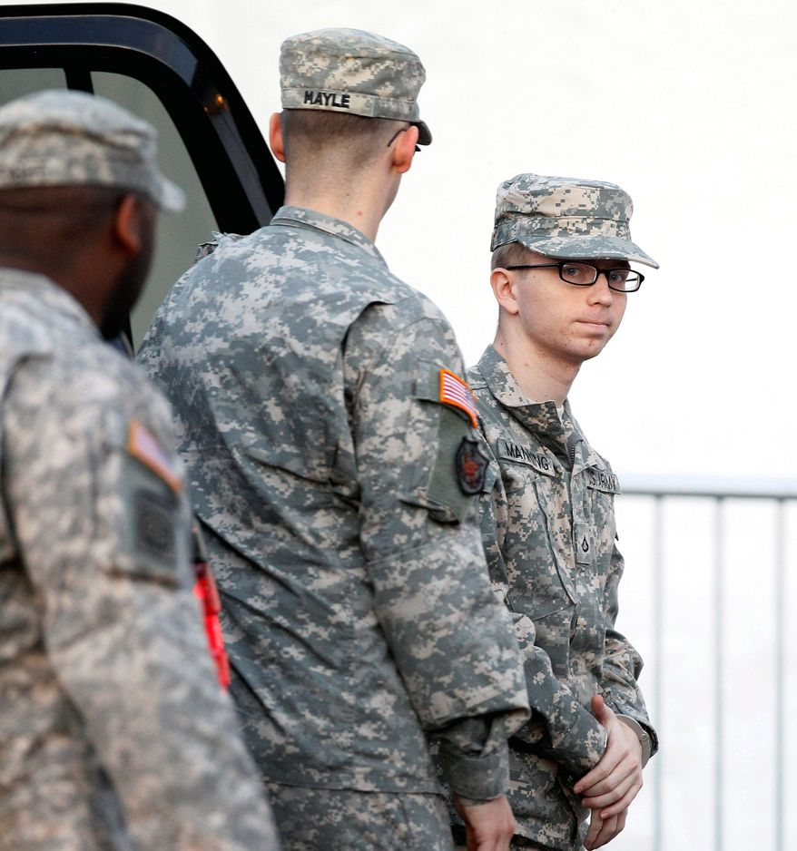 Army Pfc. Bradley E. Manning (right) is escorted from a security vehicle to a courthouse in Fort Meade, Md., on Thursday for a military hearing that will determine if he should face a court-martial in connection with a leak of secret documents. (Associated Press)