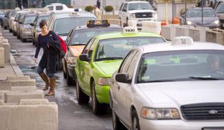**FILE** A woman walks through a line of cabs outside of Union Station in Washington, D.C. (Rod Lamkey Jr./The Washington Times)