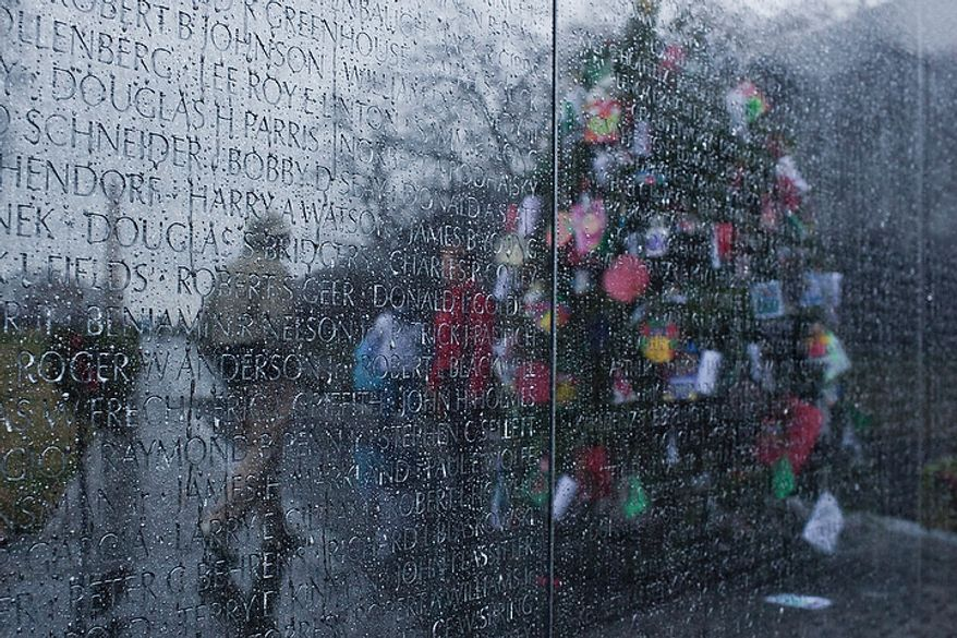 Visitors are reflected next to a Christmas tree on the rain-streaked Vietnam Veterans Memorial wall in Washington on Wednesday, Dec. 21, 2011. (T.J. Kirkpatrick/The Washington Times)