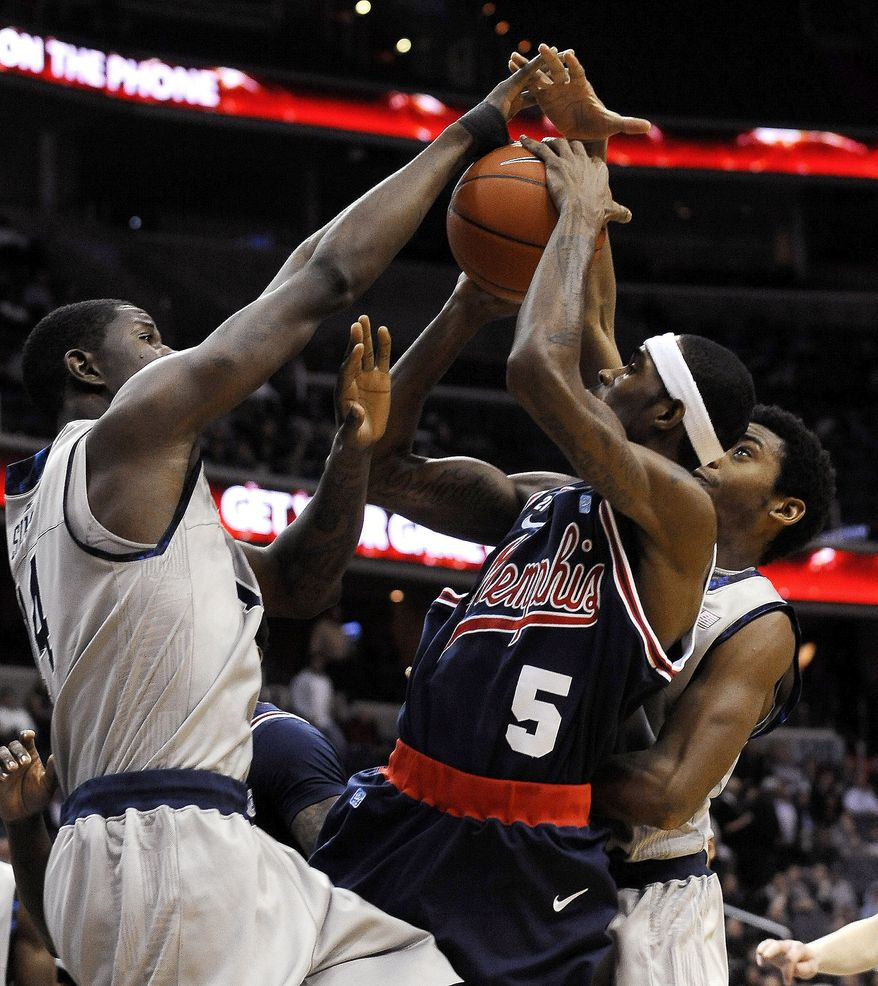 Memphis guard Will Barton (5) has his shot blocked by two Georgetown defenders, Henry Sims, left, and Hollis Thompson, right, during first half, Thursday, Dec. 22, 2011, in Washington. Georgetown defeated Memphis 70-59. (AP Photo/Richard Lipski)