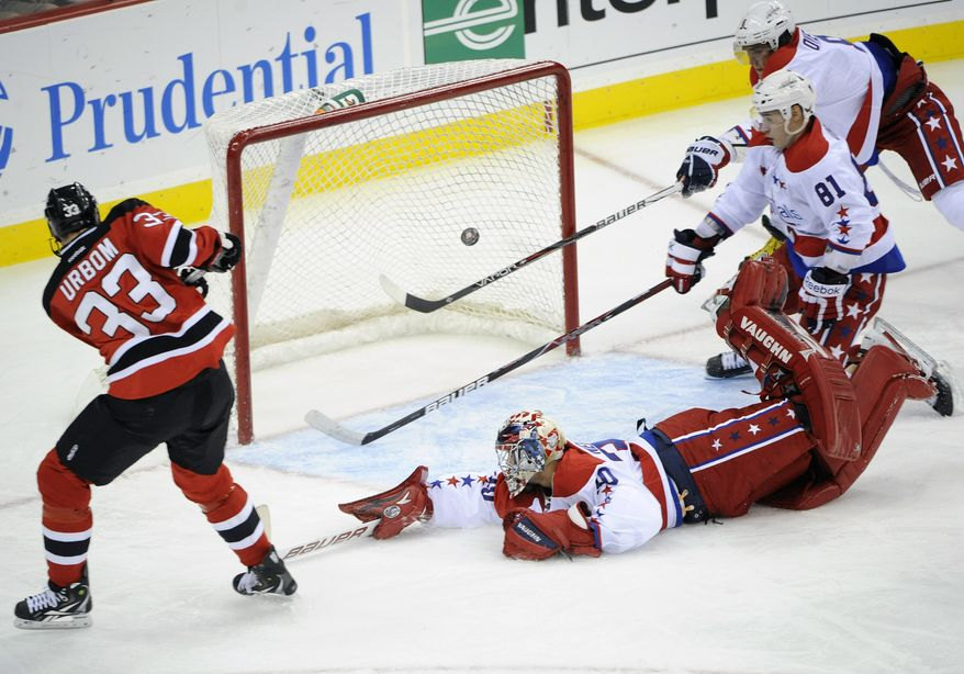 New Jersey Devils' Alexander Urbom scores a goal as Washington Capitals goaltender Michal Neuvirth, can't make the save and Dmitri Orlov and Alex Ovechkin defend during the second period Friday, Dec. 23, 2011, in Newark, N.J. (AP Photo/Bill Kostroun)