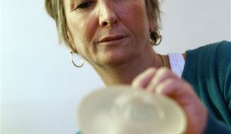In this photo taken Thursday, Dec. 22, 2011, Chantal Guerin, a 46-year-old accountant and mother of three, displays a breast implant made by Poly Implant Prothese, or PIP, that was removed from her left breast, during an interview with The Associated Press in Paris. Guerin had her left breast removed after cancer and had PIP implants put in both breasts. (AP Photo/Christophe Ena)